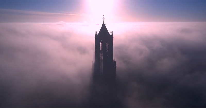 Drone Soars Above the Dom Tower of Utrecht on a Foggy Day